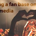 Building a fan base on social media. Hands in a crowd making a heart.