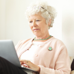 Senior woman sitting on a couch, using a laptop computer