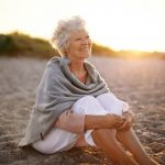 Cheerful senior woman sitting outdoors on the beach