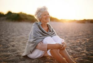 Cheerful senior woman sitting outdoors on the beach