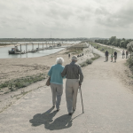 Senior Living, couple walking by the water
